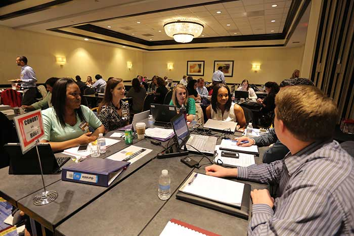 Students conversing around table during a conference session.